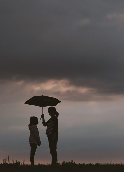 A woman holding an umbrella over a young girl