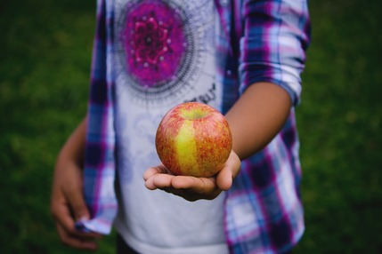 A teenager holding an apple