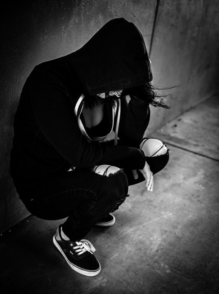 A young woman in a hoodie with her head down leaning against a wall