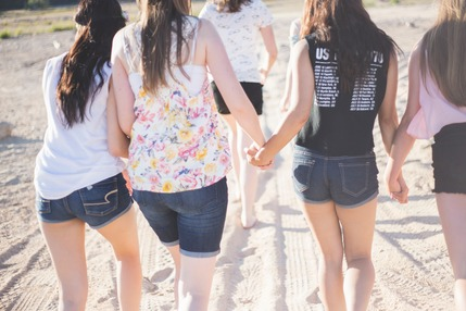 Young women walking away from the camera holding hands